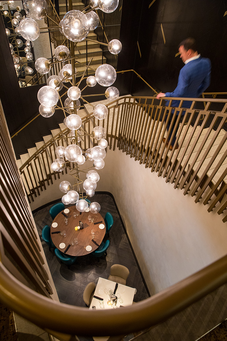 Award winning  restaurant photography of a man walking down the stairs past a hanging Chandelier