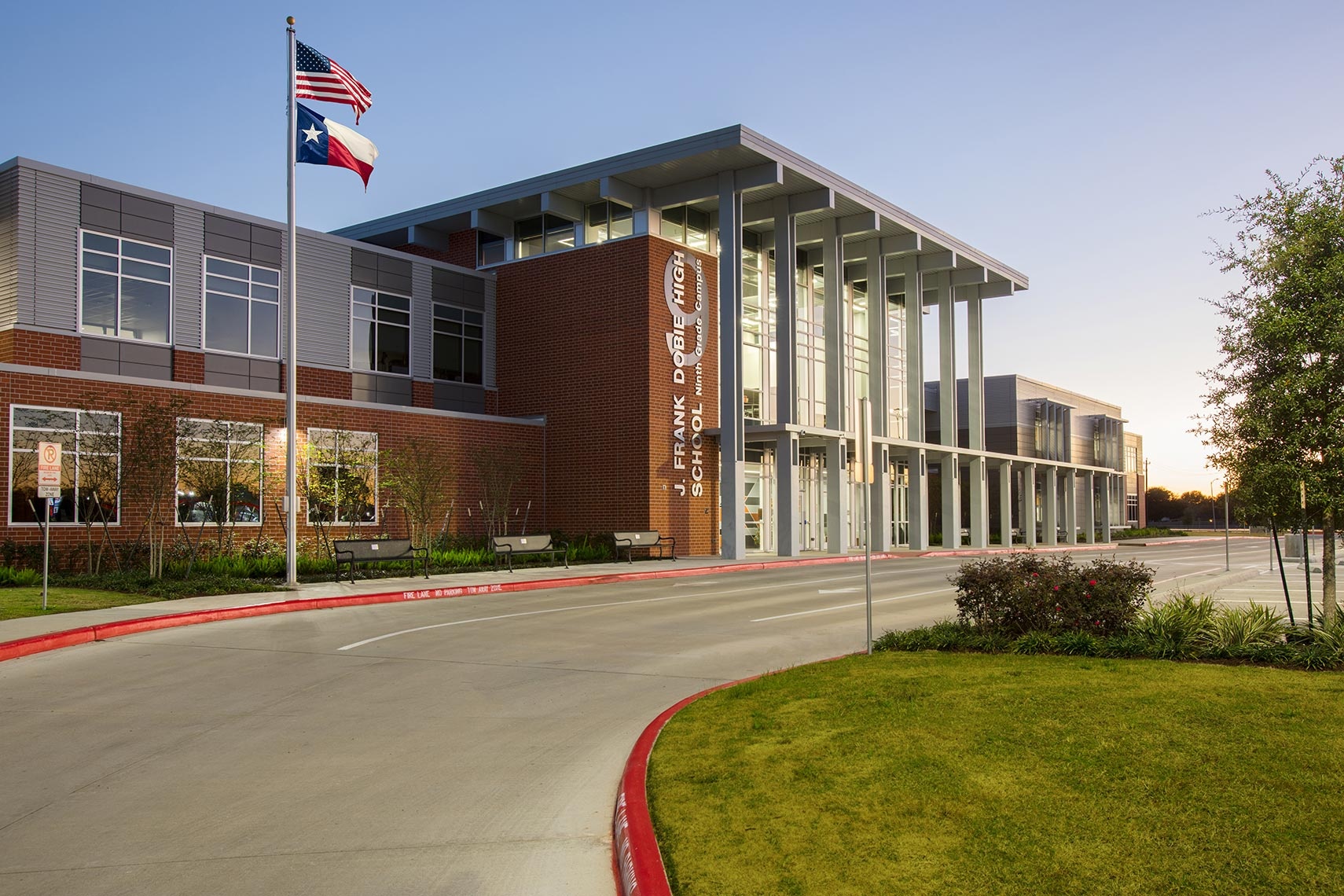 a newly constructed Texas school with American and Texas flags by the best education architecture firm photographer
