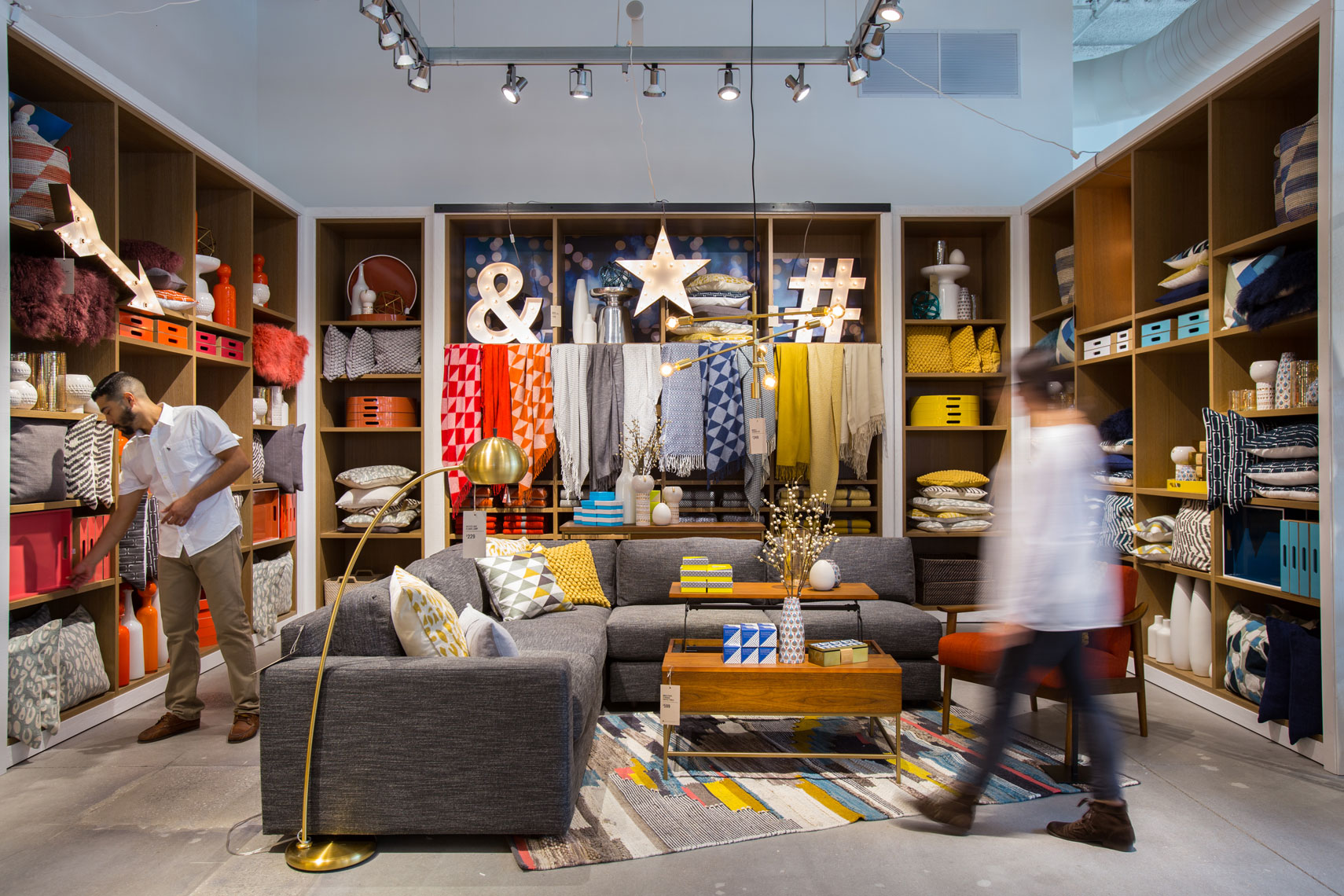 a shopper walks past a store display. An example of Retail interior design photography in Houston, Texas