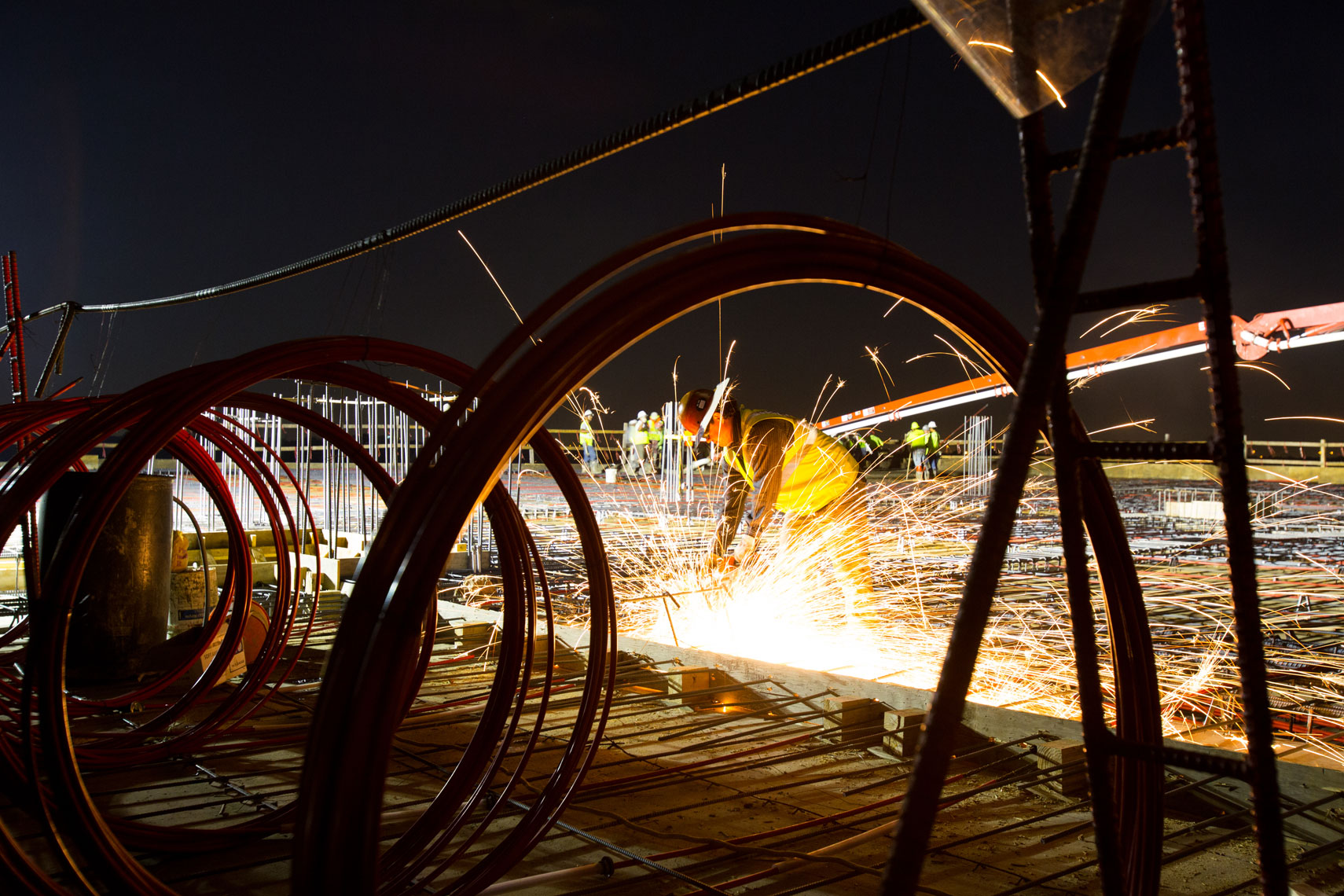 a construction worker with sparks at night by a commercial photographer in Houston Texas