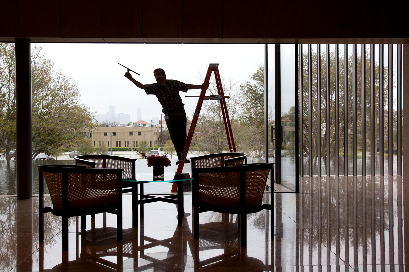 a custodian cleaning the windows of the Asia Society museum shot by an editorial photographer in Houston, Texas
