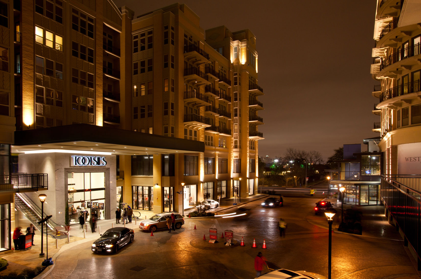 an architectural photo of a retail shopping center at night in Houston Texas